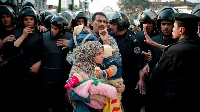 Ein Man und eine Frau mit Kind zwischen Polizisten mit Helmen.