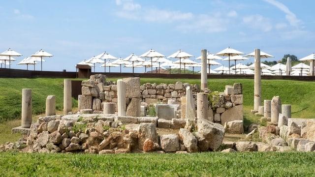 Antike Säulen vor einem Meer von Sonnenschirmen.