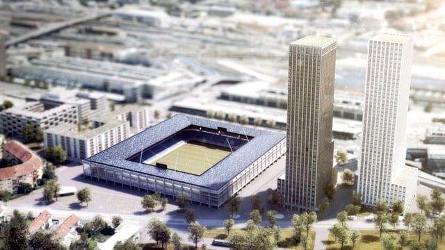 Das Modell eines Fussballstadions, daneben zwei grauweisse Hochhäuser.