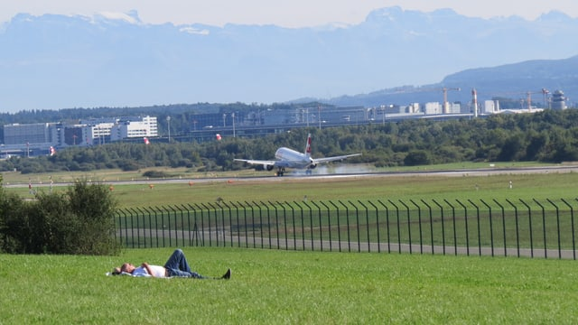 Mann im Vordergrund, Flugplatz im Hintergrund