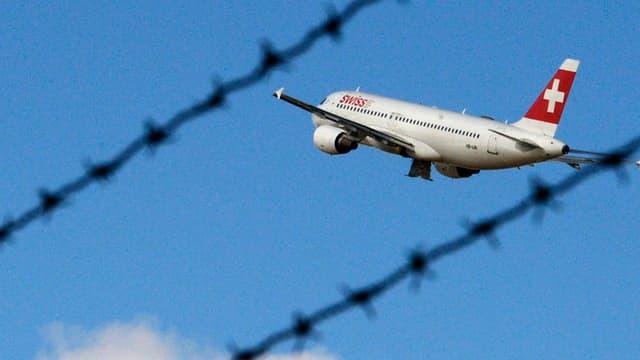 Eine Maschine der Swiss in der Luft, davor ist Stacheldraht zu sehen