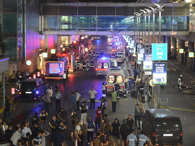 Menschenansammlung und Ambulanzautos vor Flughafen