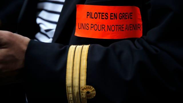 Arm eines Piloten in Uniform mit Streik-Spruch.