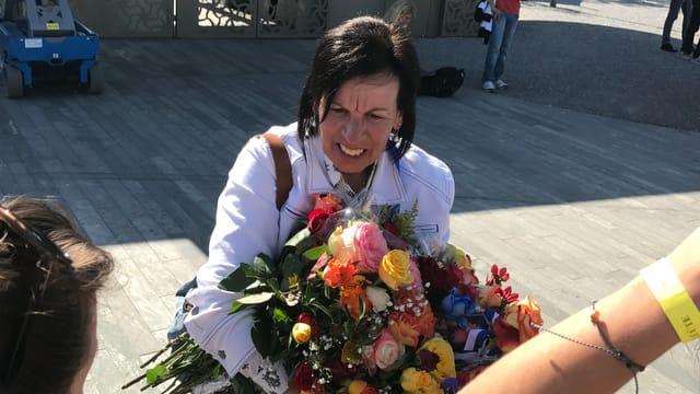 Frau mit dunklen Haaren und weisser Jeansjacke und Blumenstrauss