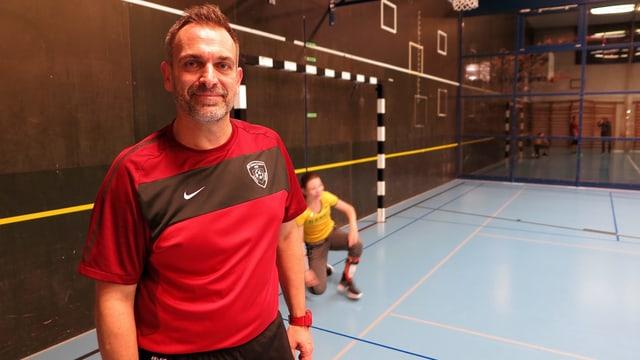 Ein Mann in einer Turnhalle. Er trägt ein rot-schwarzes Fussball-Shirt mit dem Emblem des FC Kickers Luzern.