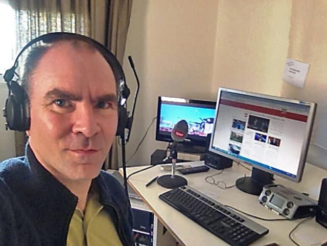 Mann mit Kopfhörern vor Schreibtisch mit Computer.