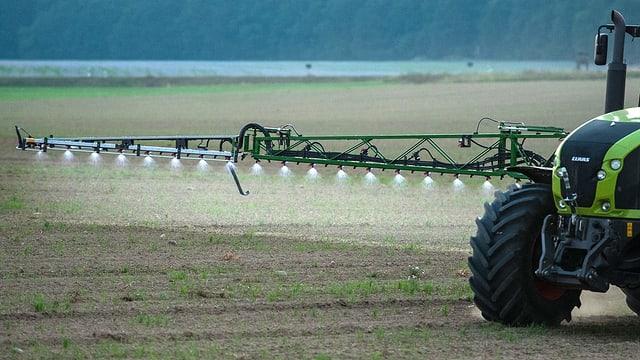 Bauer versprüht Pestizid auf Wiese.