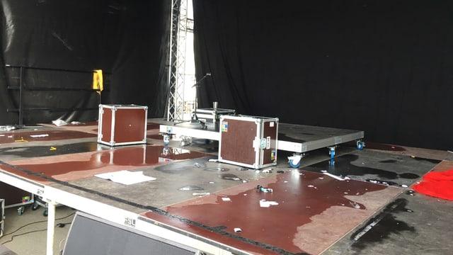 Bühne mit diversen Boxen und Wasser auf dem Boden.