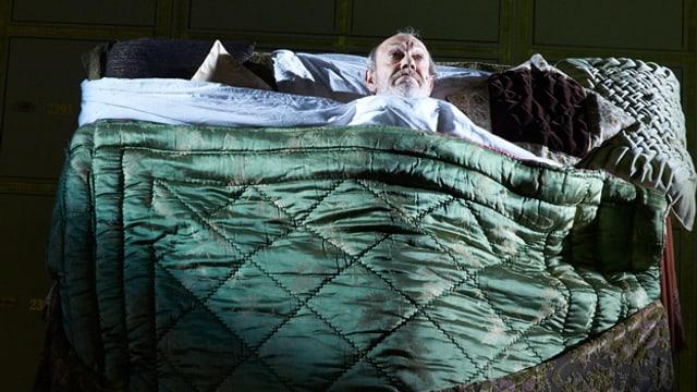 Ein Mann sitzt auf einem Stuhl, ein anderer liegt in einem hochstellten Bett.