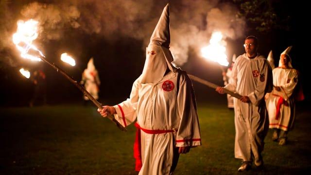 Ku-Klux_Klan Mitglieder, vermummt, bei Nacht mit Fackeln.