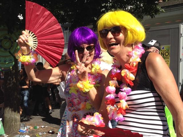 Zwei Frauen mit bunten Perücken und Fächern.
