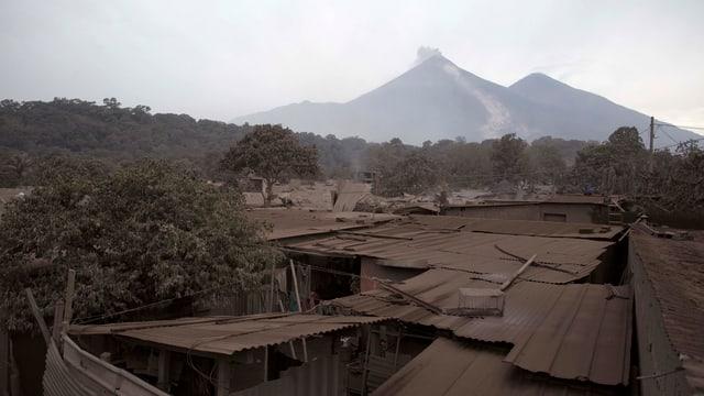 Vulkan in der Ferne, davor mit Asche bedeckte Häuser.