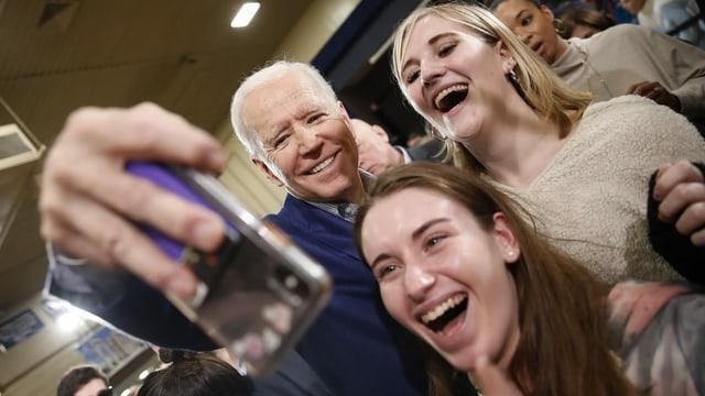 Ein älterer Mann mach zusammen mit zwei Frauen ein Selfie.