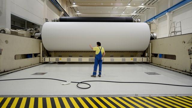 Ein Arbeiter mit einer grossen Rolle Papier