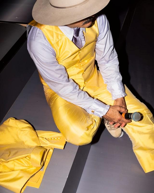 Mike Bonanno als Master of Ceremony Rocky: er trägt ein leuchtend gelben Anzug.