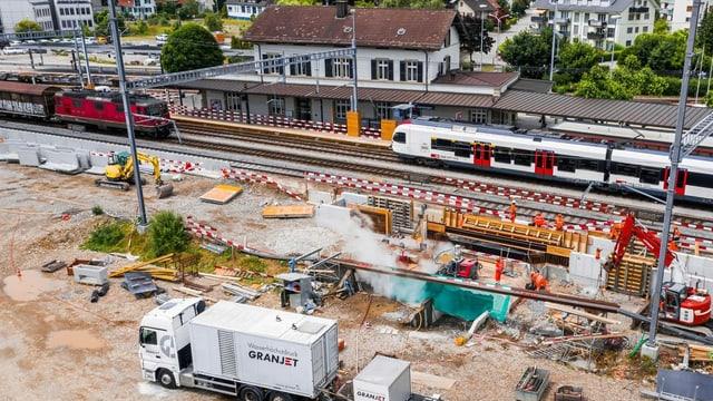 Baustelle am Bahnhof mit Zügen.