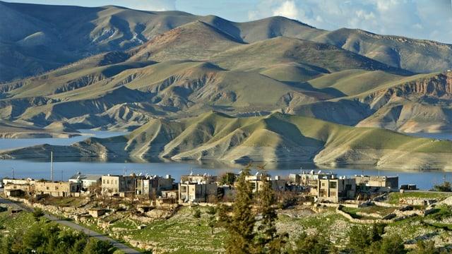 Blick auf eine kurdische Stadt vor einer Bergkette.