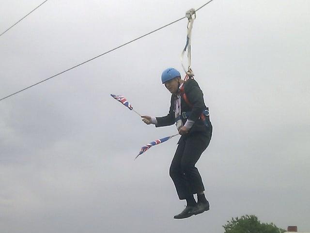 Mann hängt an Seilen und wedelt mit GB-Fahnen.