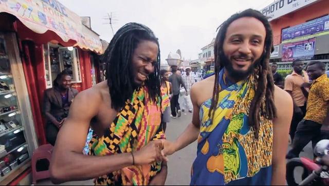 Zwei dunkelhäutige Männer mit Rastas und bunten Tüchern umgeschlungen laufen lachend durch eine belebte Strasse.