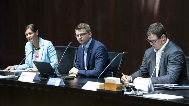 Drei SVP-Nationalräte sitzen an einem Tisch und geben eine Pressekonferenz.