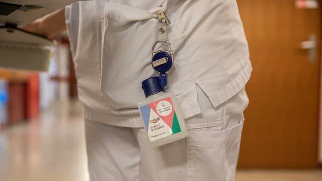 Ein Desinfektionsmittel hängt an einem Badge.