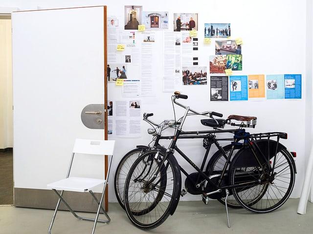 Blick in ein Büro mit einer Wand, an die diverse Artikel gepinnt und Post-Its geklebt sind, davor zwei Velos und ein Stuhl.