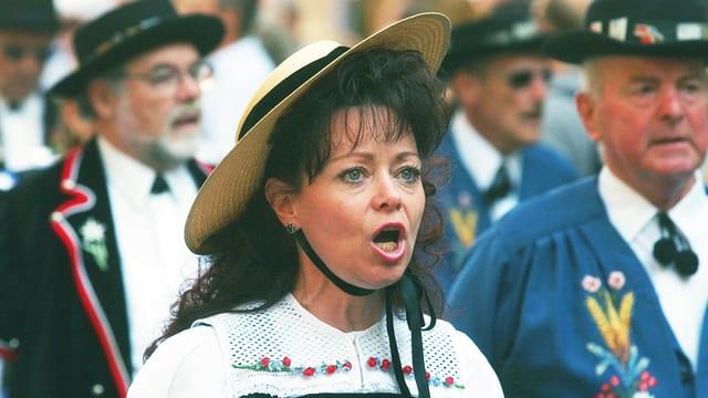 Eine Frau in Schweizer Tracht singt.