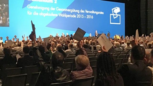 Ein Saal mit Menschen die ihre Stimmzettel in die Höhe halten.
