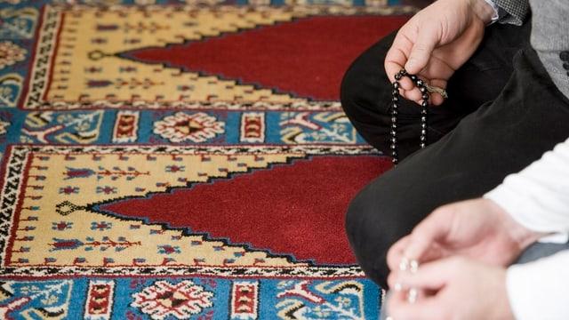 Zwei Männer, von denen nur Hände und Knie zu sehen sind, knien mit Gebetsketten auf Gebetsteppichen.