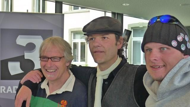 Zu sehen sind drei Männer. Ein junger Mann im Teeshirt und Bürstenhaarschnitt, ein Mann um die 45 Jahre alt mit Beret und ein angegrauter Mann, der wie 65 aussieht, mit Bärtchen und Brille.