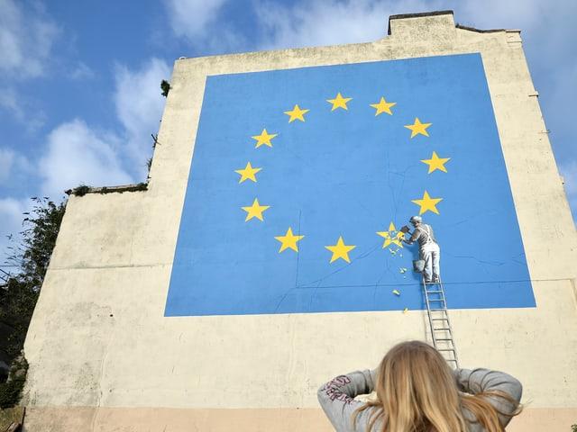 Darauf zu sehen ist eine mehrere Meter hohe quadratische EU-Flagge, aus der ein Handwerker einen Stern heraus meisselt.
