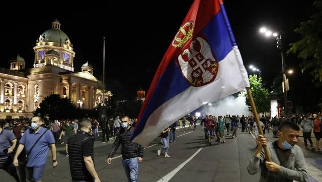 Demonstranten mit Serbischer Fahne vor dem Parlamentsgebäude in Belgrad.