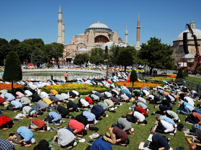 Zahlreiche Männer beten vor der Hagia Sophia.