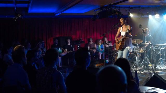 Eine Musikerin steht mit Gitarre auf der Bühne und singt vor Publikum.