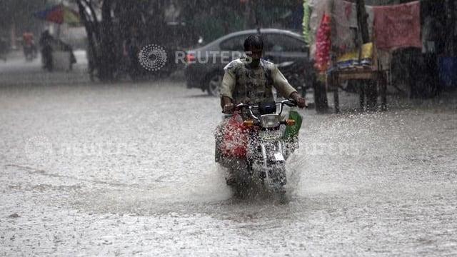 um che va cun moped tras via inundada a pakistan
