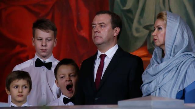 Familie Medwedew beim Gottesdienst, ein Sohn gähnt.