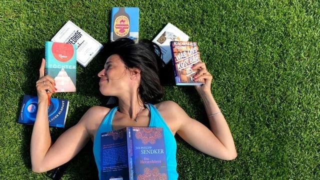 Annette König liegt in der Wiese. Um ihren Kopf Bücher.