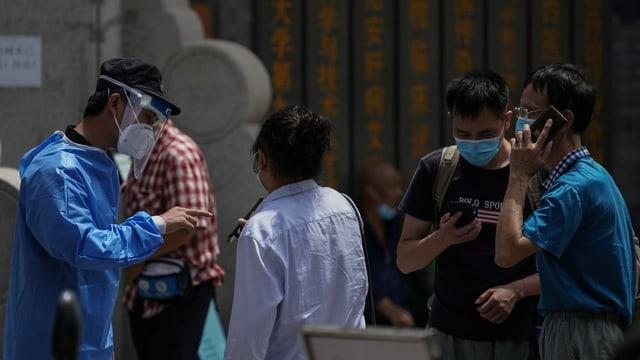 Purtret da Chinais che spetgan davant in post per pudair sa testar sin il coronavirus.