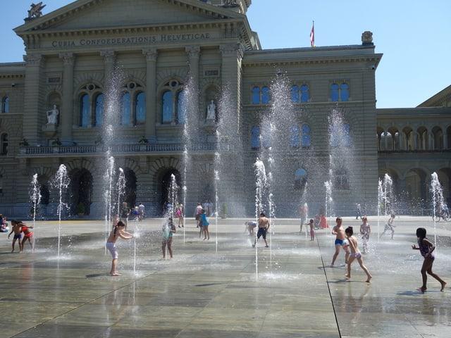 Kinder spielen unter den Wasserspiel beim Bundeshaus.
