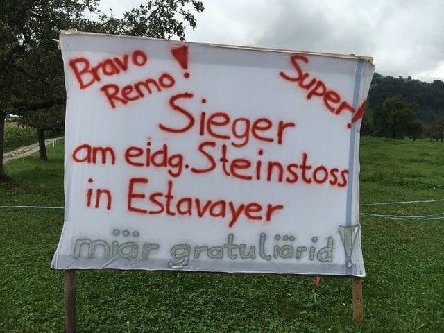 Ein grosses Transparent empfängt den Steinstoss-Sieger zu Hause.
