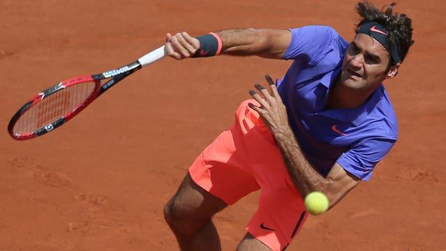 Federer che en il gieu da tennis. El ha en in t-shirt violet e chautschas da colur da cural.