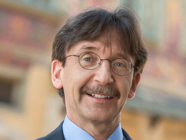 Ein Mann mit braunen Haaren, Schnurrbart und runder, feiner Brille.