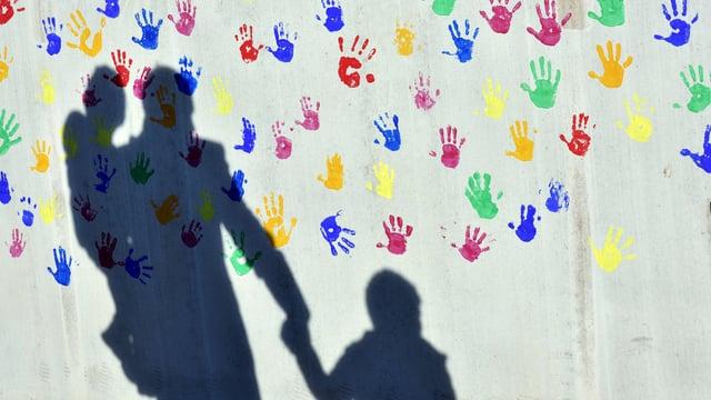 Ein Vater mit einem Kind auf dem Arm und einem an der Hand