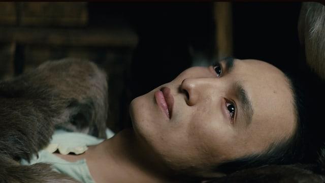 Ein Inuit Mann liegt mit Tränen in den Augen.