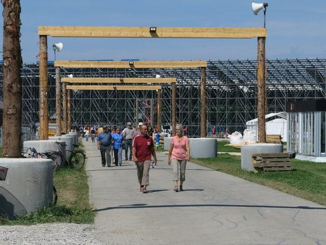 Eine Strasse mit Menschen, im Hintergrund die Arena der Schwinger.