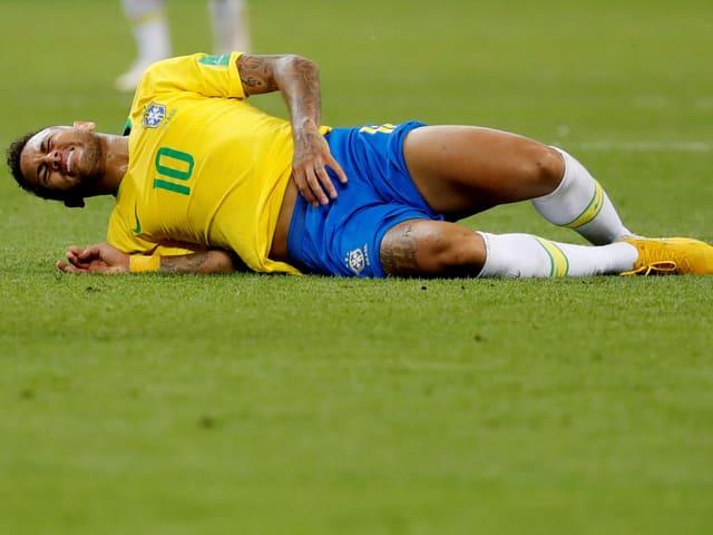 Neymar liegt mit schmerzverzerrter Miene auf dem Boden.