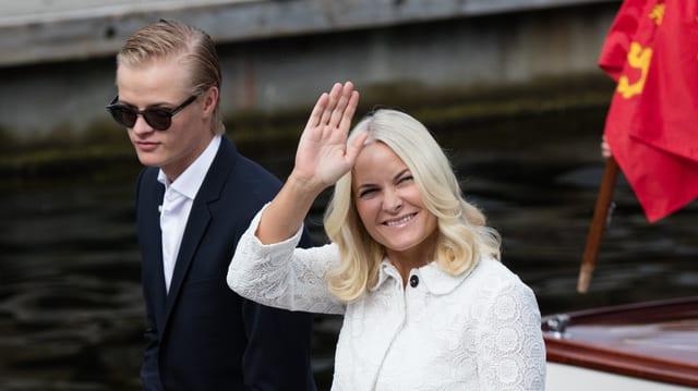 Marius Borg Høiby mit Sonnenbrille und Anzug, Mette-Marit im weissen Mantel.