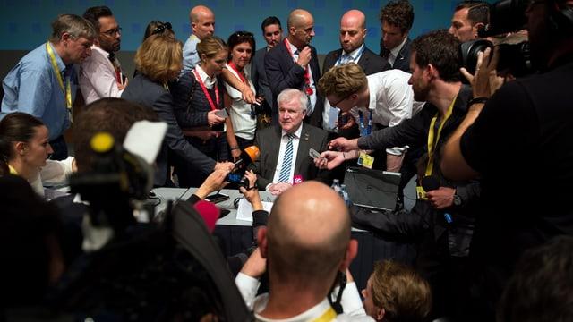 Horst Seehofer umgeben von zahlreichen Journalisten und Fotografen