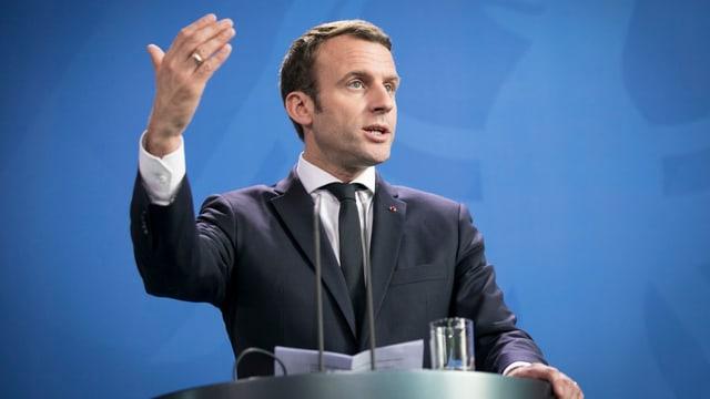 Macron vor blauem Hintergrund an einem Rednerpult, er gestikuliert.