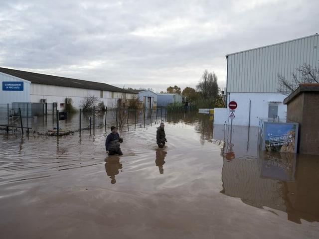 Zwei Personen waten in den überschwemmten Vorhöfen.